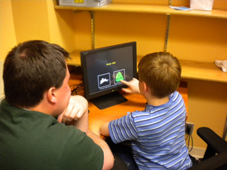 Staff member and child doing an activity on a computer