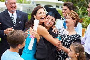 Family congratulating and hugging student at graduation