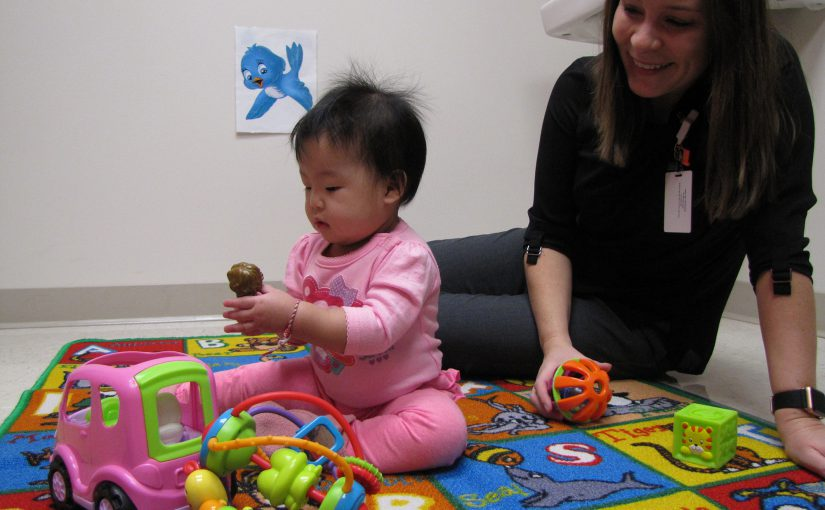 A baby plays with toys in the lab.