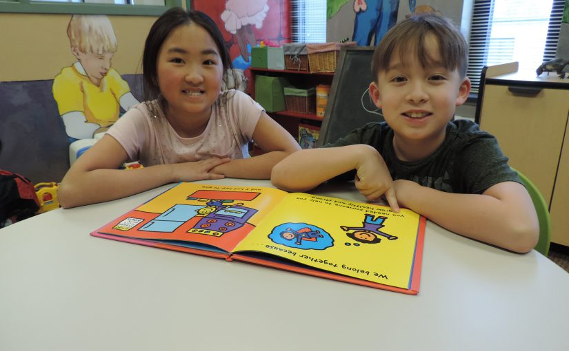Two children smiling while pointing to a book.