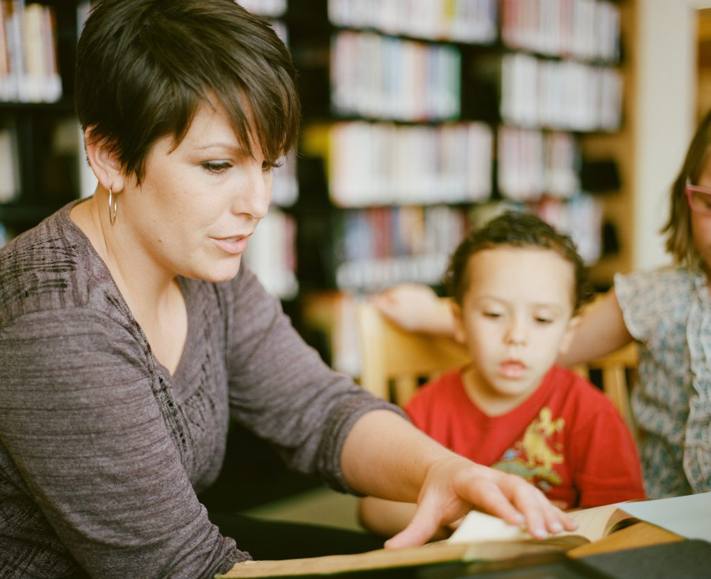 Educator helps young child read